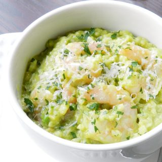 Avocado Shrimp Risotto in a white bowl. topped with grated Parmesan cheese.