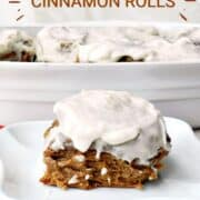 gingerbread cinnamon roll on a white plate sitting on a red napkin with a pan of rolls in the background.