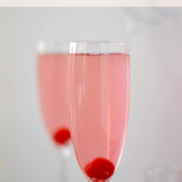 Kinky Bubbles Cocktail in a champagne flute with a cherry at the bottom
