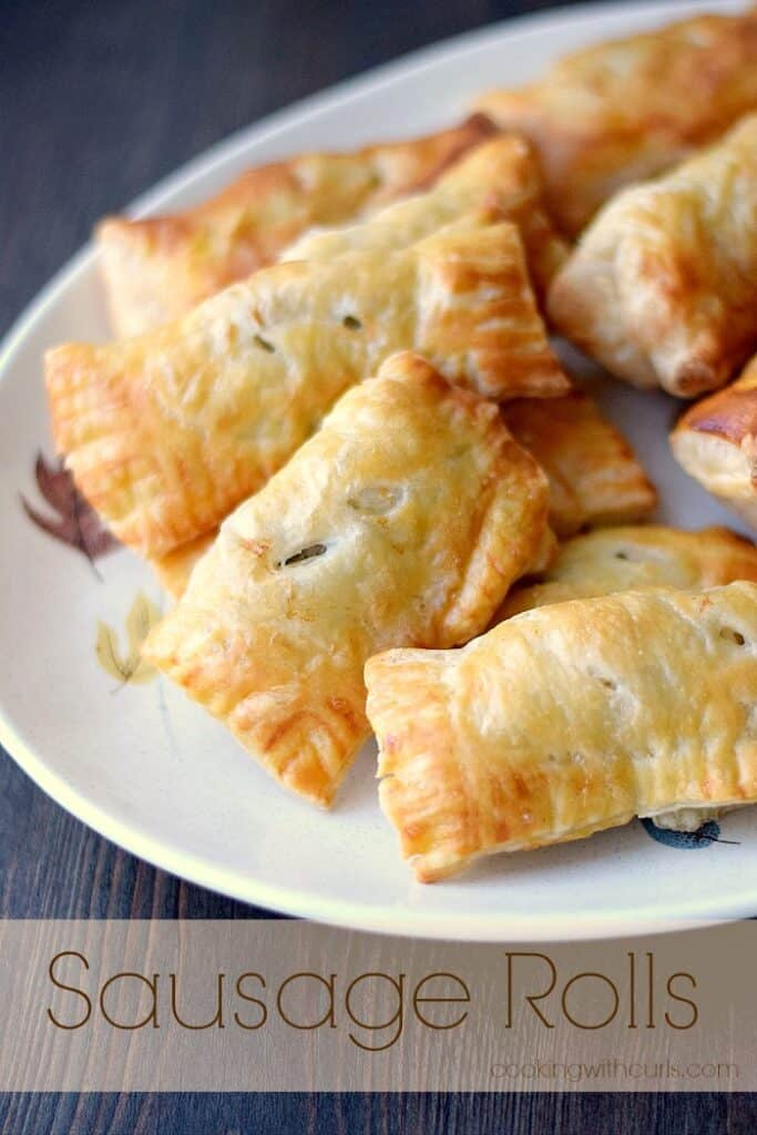 sausage rolls wrapped in puff pastry piled up on a beige plate with a falling leaves motif