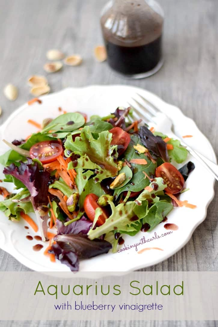 a tossed Aquarius Salad with Blueberry Vinaigrette on a white plate with a bottle of dressing in the background