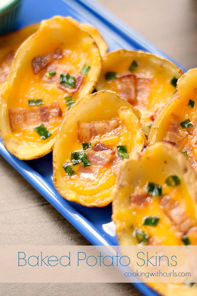 potato skins topped with bacon and green onions spread out on a rectangle blue plate