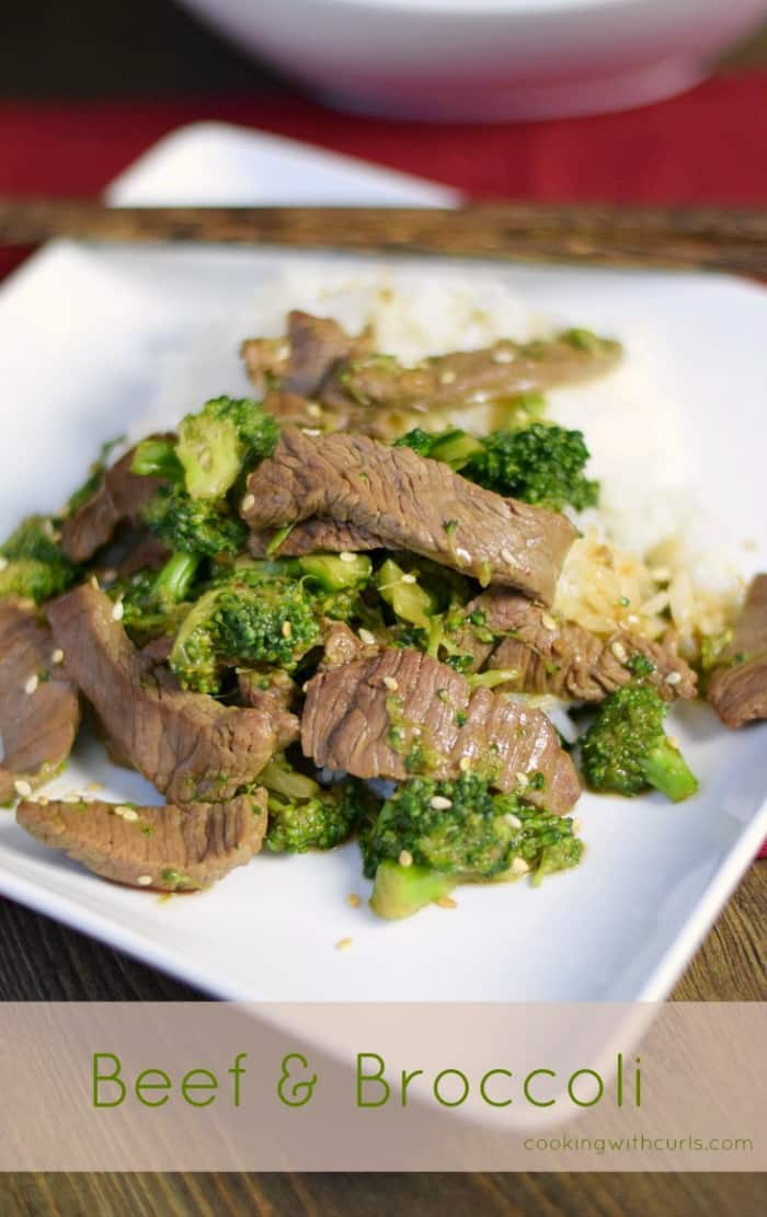 beef strips and broccoli top a bed of white rice sitting on a square white plate with chop sticks in the upper corner