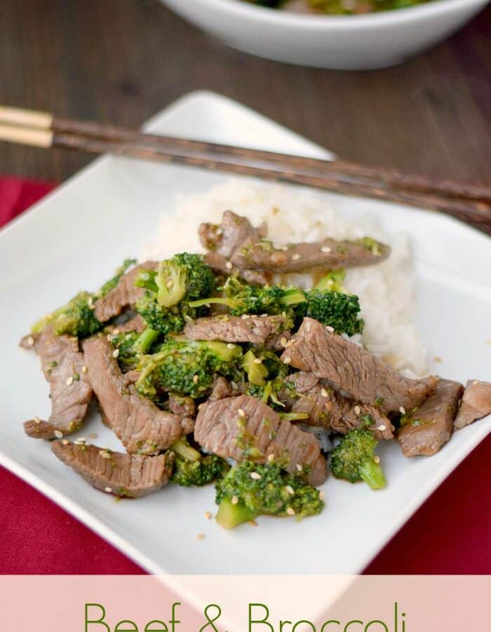 beef strips and broccoli on a bed or white rice centered on a square white plate that is resting on a red napkin