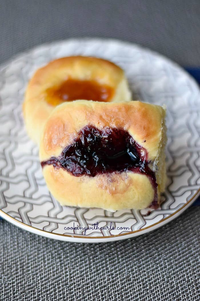 blueberry and apricot kolaches sitting on a gray and white zigzag patterned plate