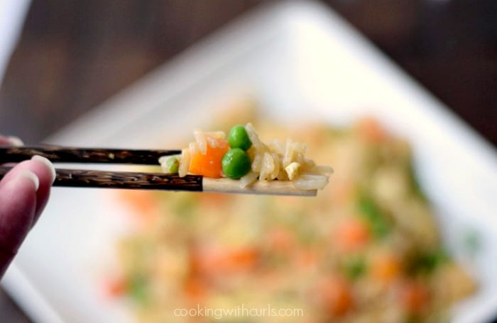 close up image of fried rice, carrots and peas on wooden chopsticks