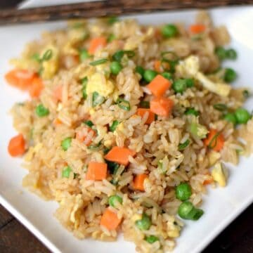 fried rice on a square white plate with two wooden chopsticks resting across the top of the plate