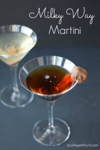 One dark Milky Way Martini in a martini glass with a light colored martini in the background