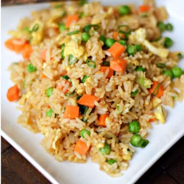 Rice mixed with soy sauce, scrambled eggs, peas, carrots, and green onions on a square plate.