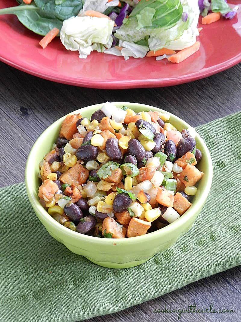 Black Bean Salsa with roasted corn and sweet potato in a small green bowl