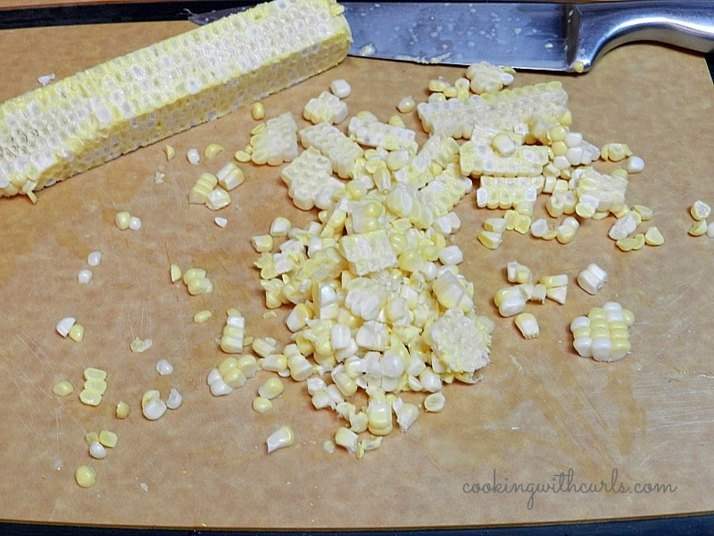 corn kernels cut off the cob sitting on a cutting board