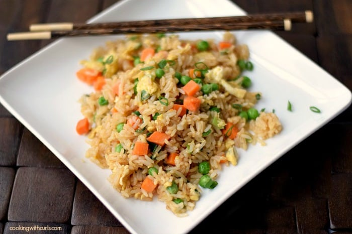 a serving of fried rice on a square white plate with two wooden chopsticks laying across the top corner of the plate