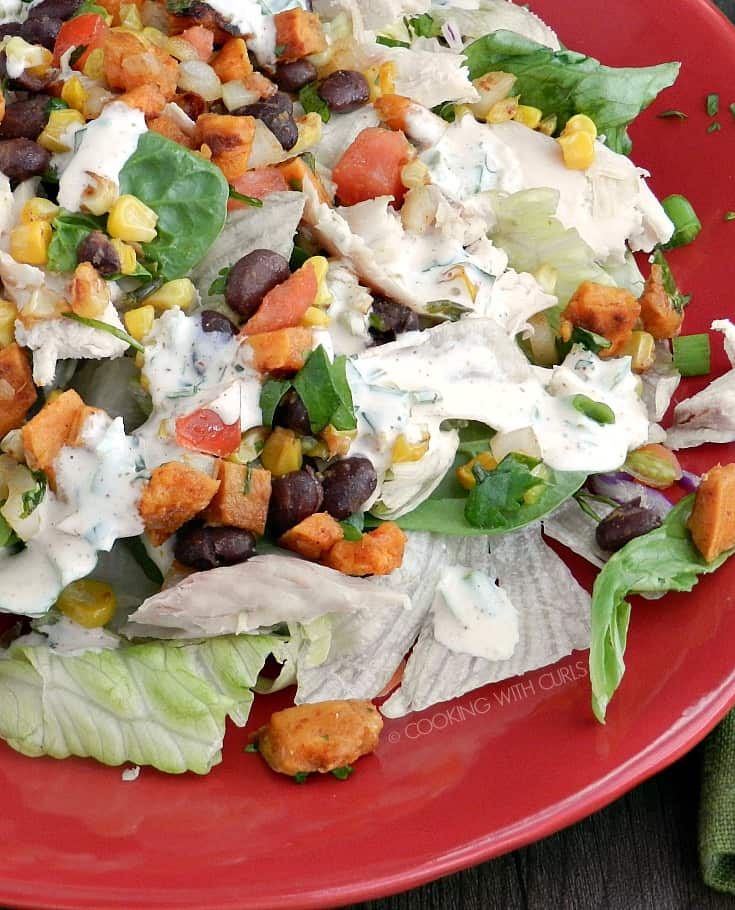 A close up of a Southwest Chicken Salad for Fall with roast sweet potato and corn topped with chipotle ranch dressing