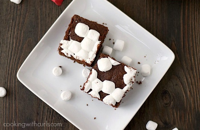 two marshmallow covered brownies sitting on a square white plate