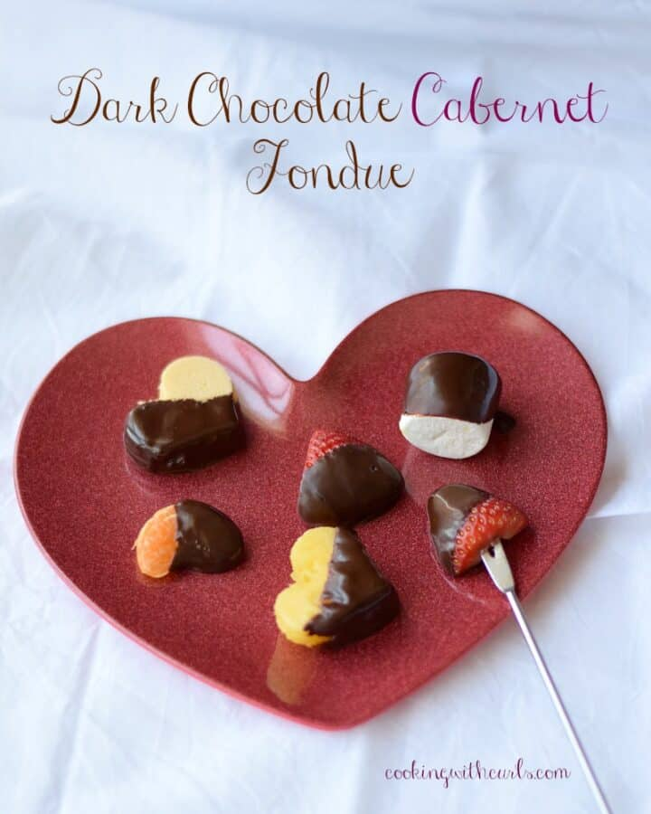 Dark Chocolate Cabernet Fondue covered fruits and marshmallows siting on a red heart shaped plate.