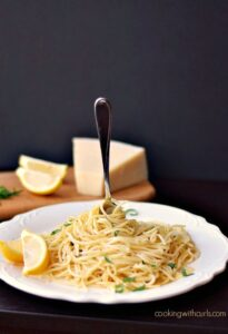 spaghetti noodles swirled on a white plate with a fork stuck in the middle and a wedge of parmesan in the background
