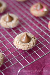 Chocolate Peanut Butter Kisses Cookies on a wire rack over a dark pink napkin