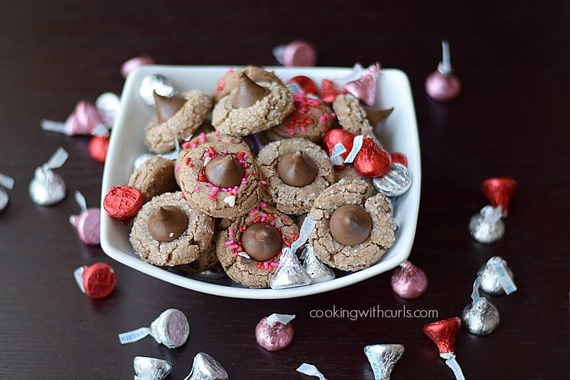 a white bowl full of Chocolate Peanut Butter Kisses Cookies and pink, red and silver wrapped Hersheys Kisses
