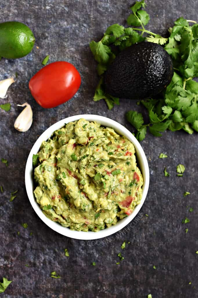 Looking down on a bowl of guacamole with a lime, tomato, garlic cloves and cilantro leaves in the background.