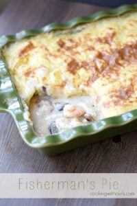 mashed potato topped fish pie in a dark green baking dish sitting on a dark brown table