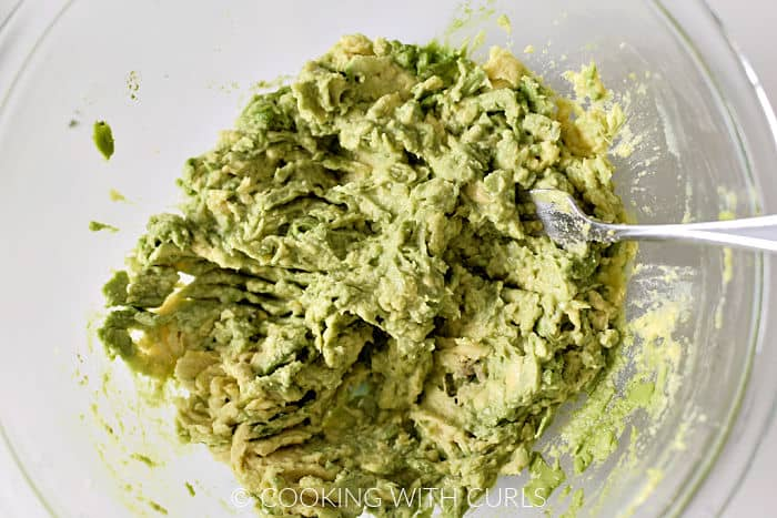 Mashed avocado in a large glass bowl with a fork.