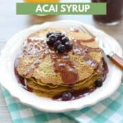 Matcha Pancakes with Pomegranate Acai Syrup served on a white plate sitting on a turquoise and white check napkin with orange juice and syrup in the background and title graphic across the top.