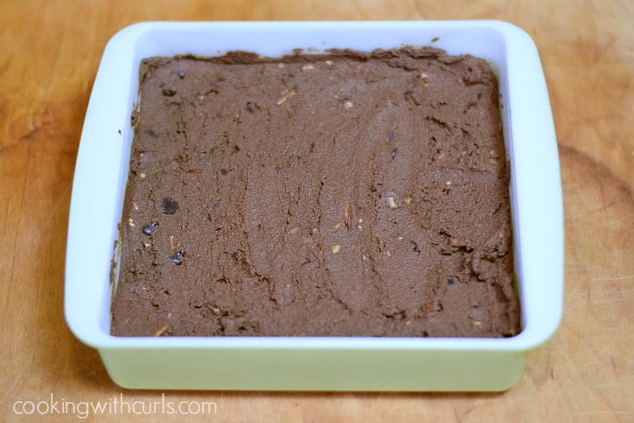 a square green baking dish with the brownie mixture inside