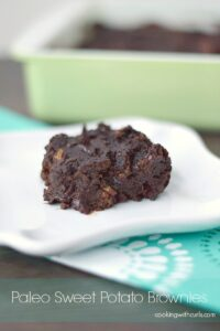 paleo sweet potato brownie on a square white plate with a green baking dish in the background