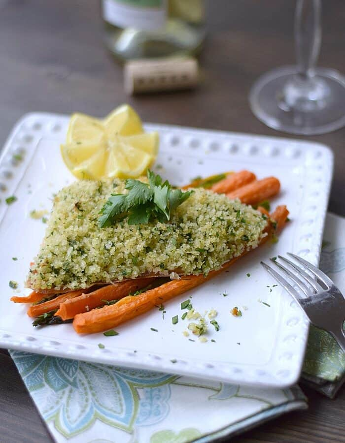 Rosemary and Panko Crusted Salmon on a bed of carrots and asparagus with a carved lemon half in the corner of a square white plate.