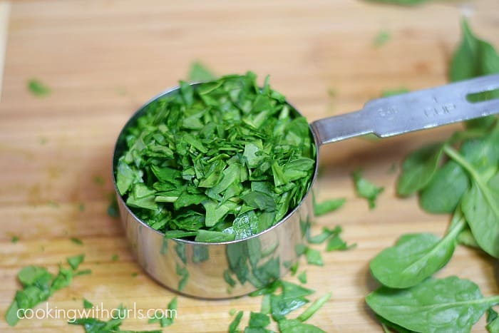 chopped spinach in a stainless steel measuring cut sitting on a wooden cutting board