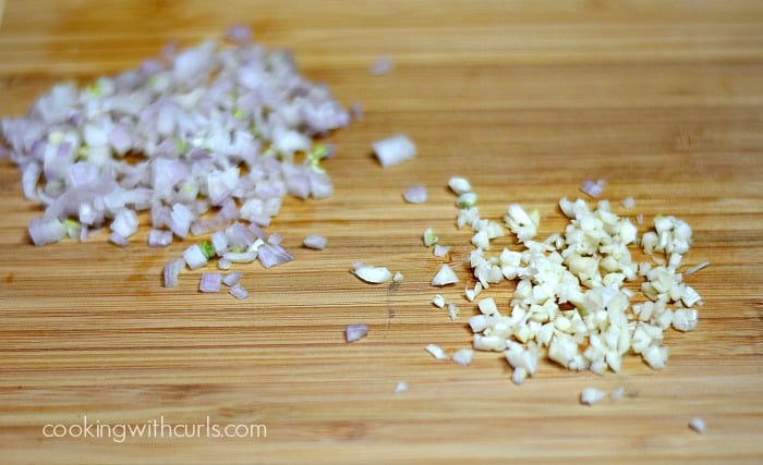 minced shallots and garlic on a wood cutting board