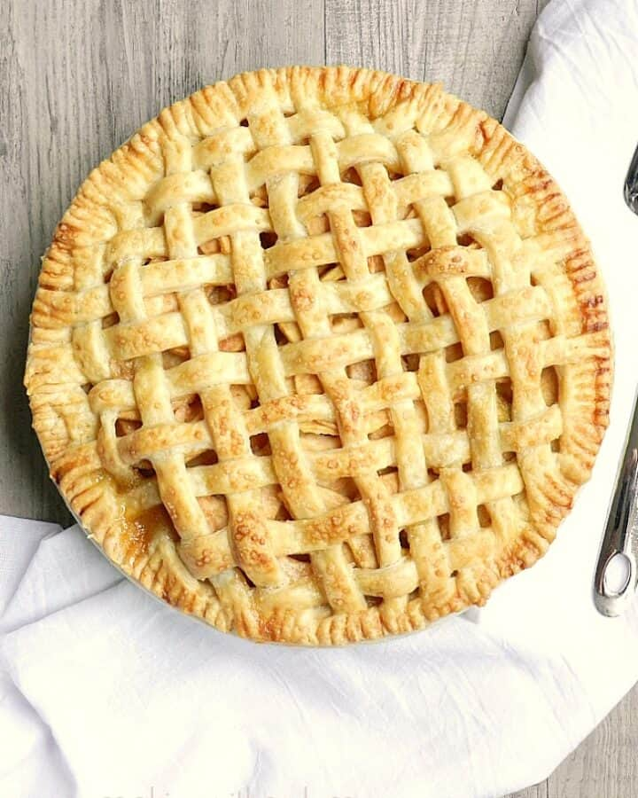 lattice top apple pie on a wood table with a white towel and silver pie server on the side