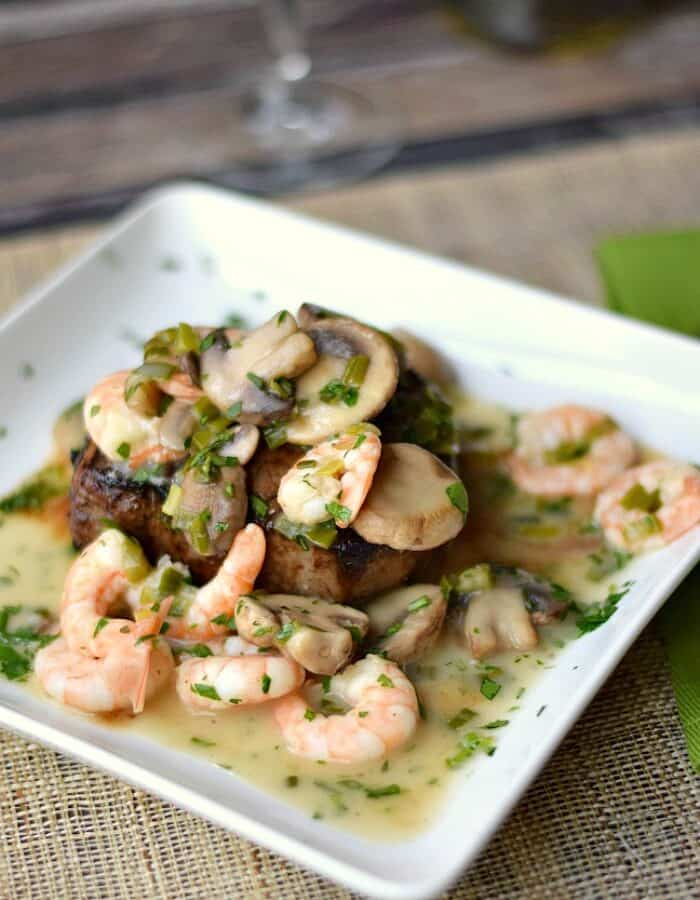 Beef Tenderloin with Shrimp and Mushroom Sauce on a square white plate