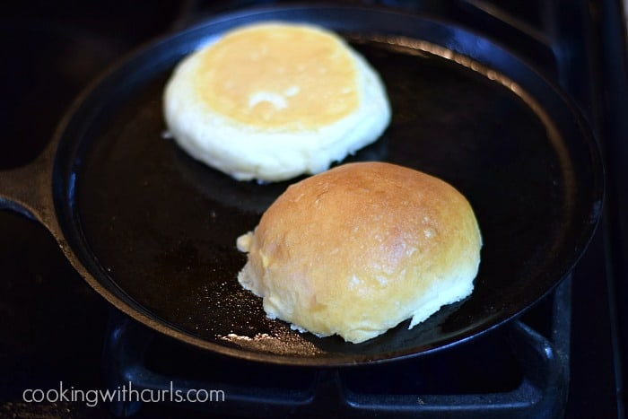 Two hamburger bun halves getting toasted in a cast iron skillet.