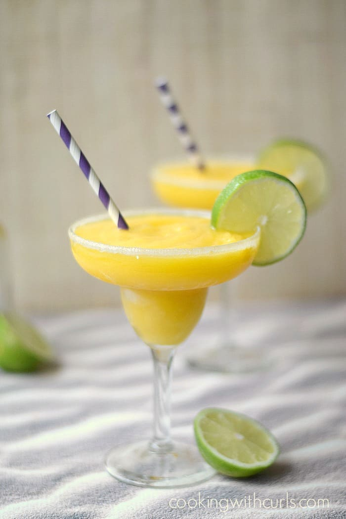 two frozen mango margaritas in sugar rimmed glasses with purple and white striped straws and a lime slice