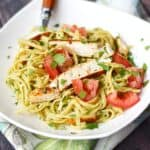 Guacamole Linguine with Chicken in a square white bowl with a wood handled fork in the upper left corner.