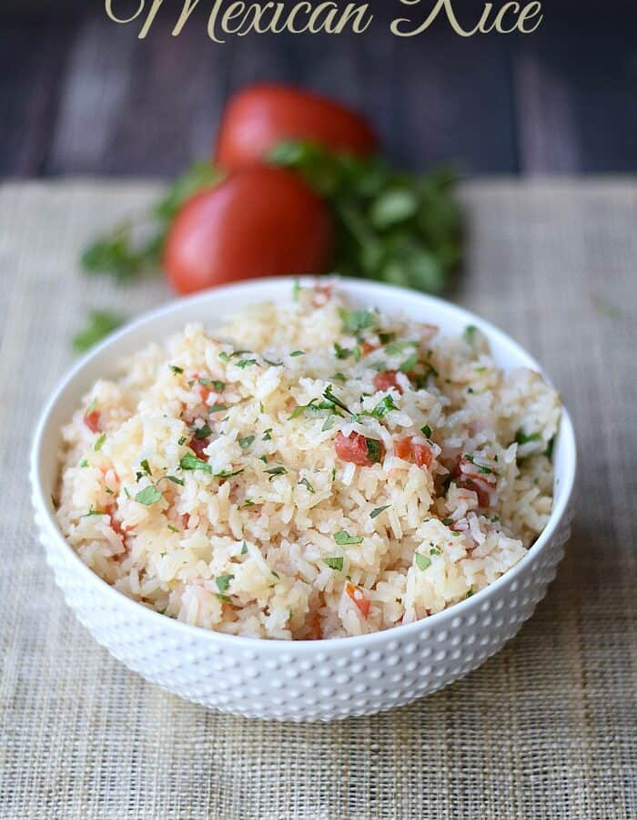 Mexican Rice in a white bowl with tomatoes in the background.