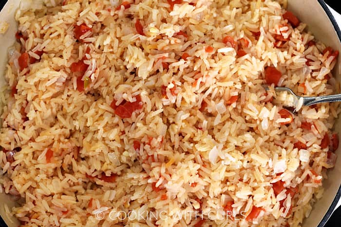 Mexican Rice fluffed with a fork in a large skillet.