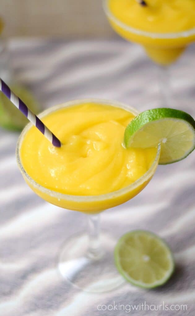 blended mango margaritas in sugar rimmed margarita glasses with a purple and white striped straw and a slice of lime