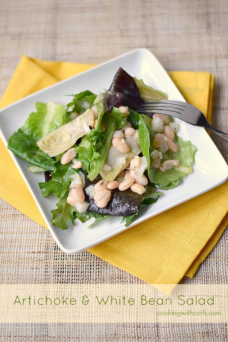 Artichoke and White Bean Salad on a square white plate sitting on a bright yellow napkin