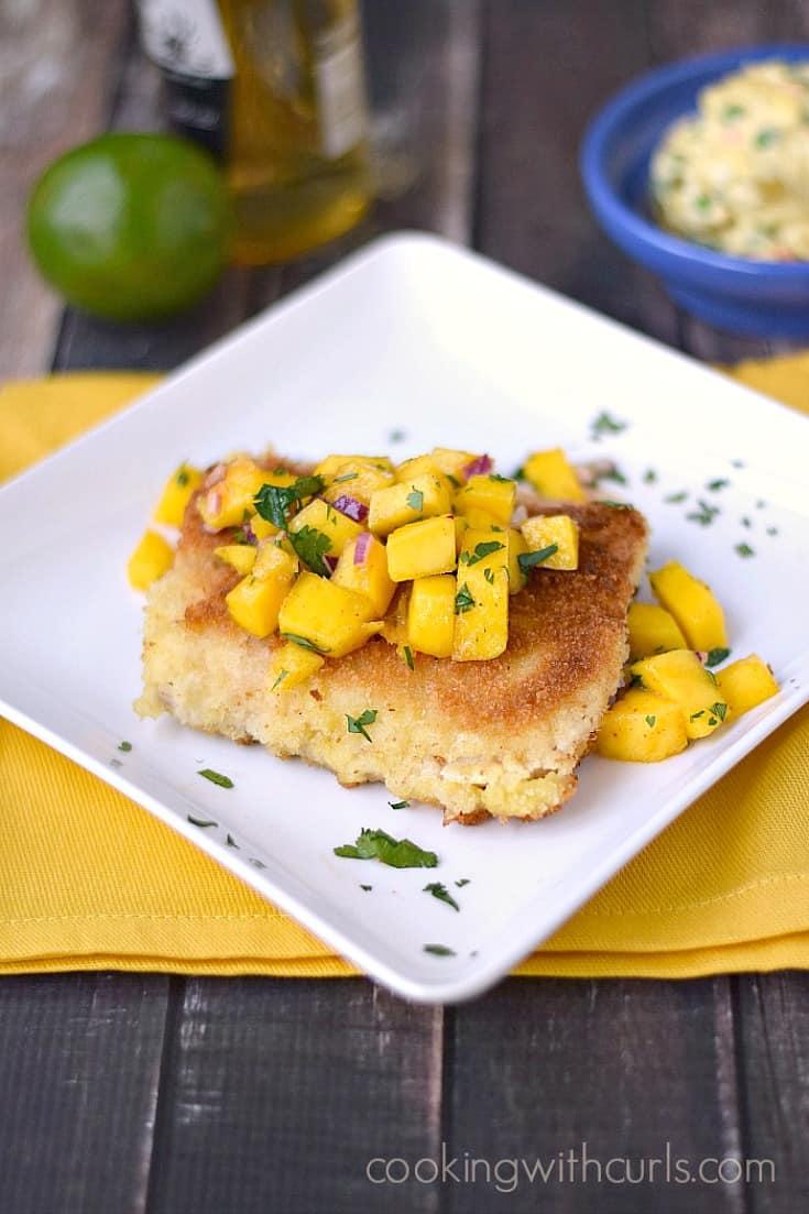 Mahi Mahi with Panko coating and topped with Papaya mango Salsa sitting on a bright yellow napkin.
