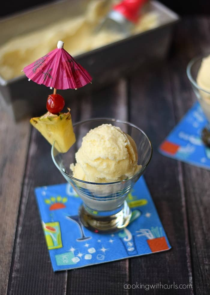 Piña Colada Ice Cream in a small glass garnished with a piece of pineapple, a cherry and pink paper umbrella.