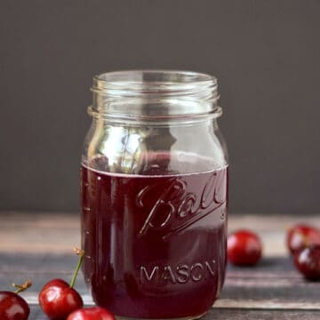 Cherry Simple Syrup in a glass mason jar surrounded by fresh cherries.
