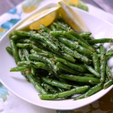 French Green Beans {Haricot Verts} in a white serving dish with lemon wedges on the side.
