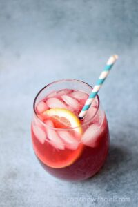 Passion Tea Lemonade in a small glass with a blue and white striped paper straw