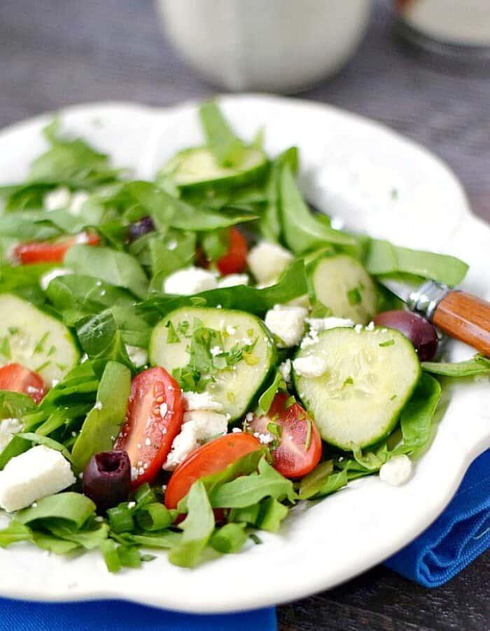 A fresh Greek Salad on a white plate sitting on a bright blue napkin