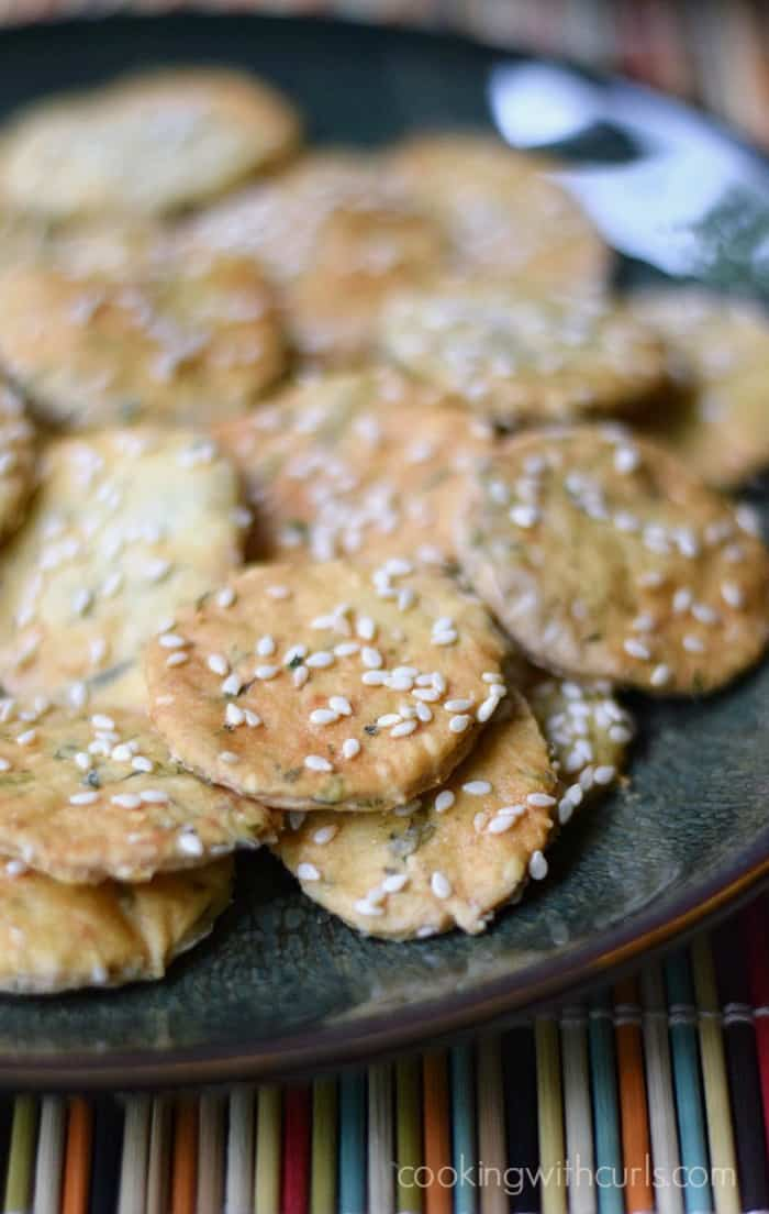 Crispy and delicious Sesame Crackers piled on a dark plate