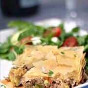 Greek Summery Meat Pie on a white plate with a Greek salad on the side and title graphic across the top.