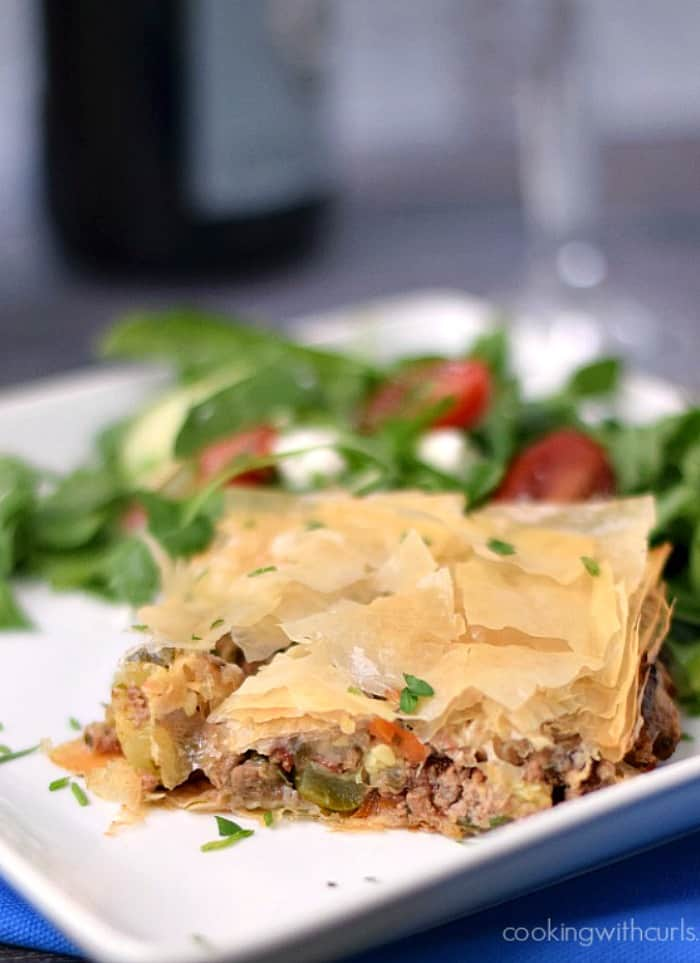 Greek Summery Meat Pie on a white plate with a Greek salad on the side