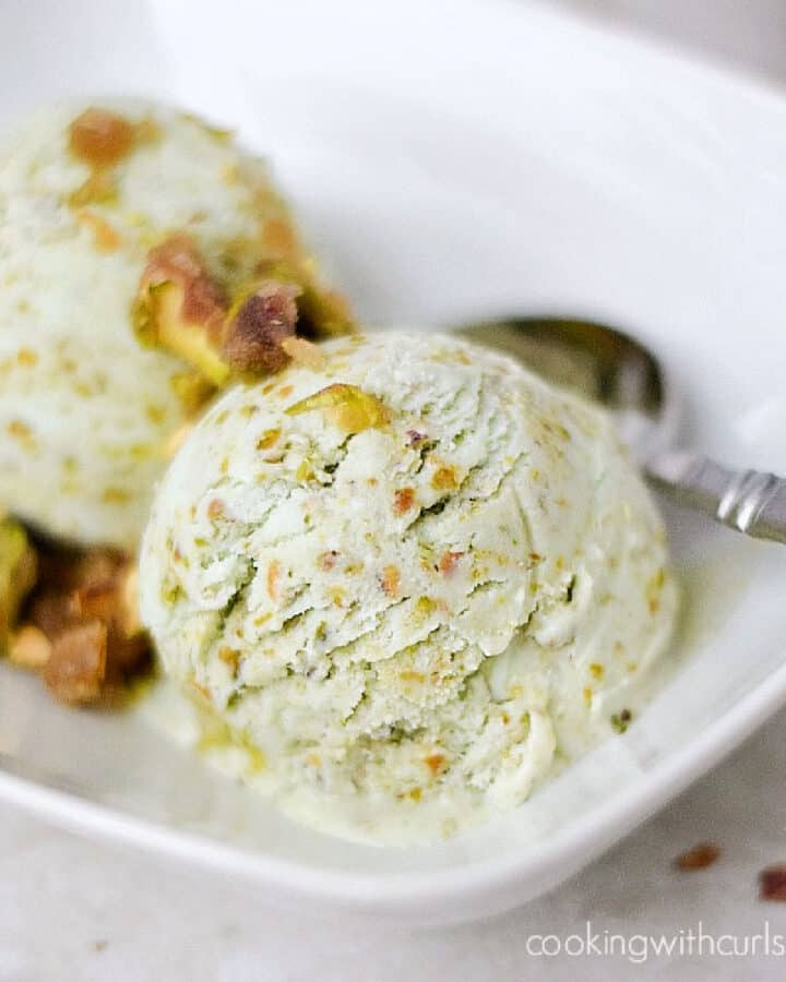 Pistachio Ice Cream topped with Pistachio Praline in a white rectangle dish with a spoon on the side.